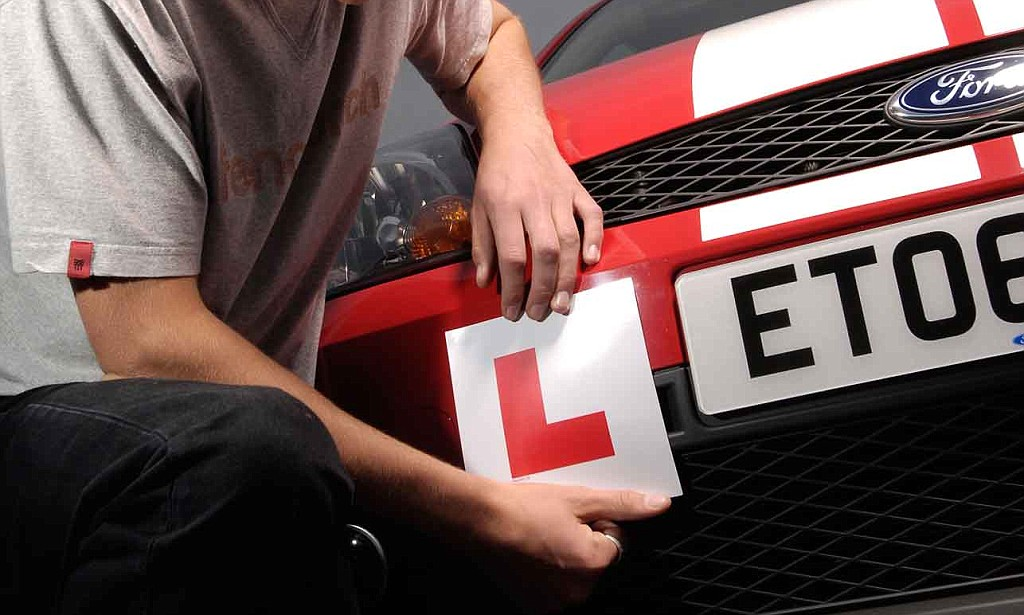 driver putting L plates on car