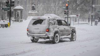 Бездомный помог водителям вытолкать застрявшую в снегу машину, подложив под колеса свое одеяло